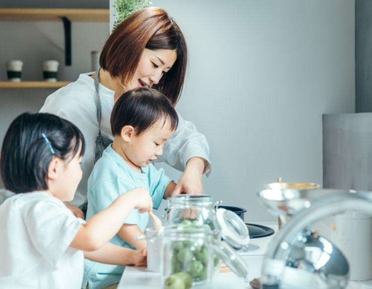 キッチンで子供に料理を教える母